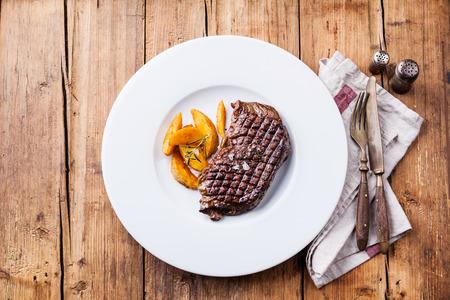 목조 배경에 하얀 접시에 구운 된 감자 웨지와 구운 된 남미 프리미엄 쇠고기 뉴욕 스테이크