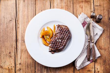 Grilled South American premium beef New York steak with roasted potato wedges on white plate on wooden background