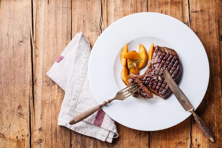 목조 배경에 하얀 접시에 구운 된 감자 웨지와 구운 된 남미 프리미엄 쇠고기 뉴욕 스테이크 스톡 콘텐츠 - 33126849