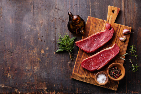 어두운 나무 배경에 원시 신선한 고기 Striploin 스테이크와 조미료 스톡 콘텐츠