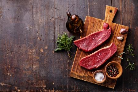 carnicero: Raw fresco Lomo de filete de carne y los condimentos en el fondo de madera oscura