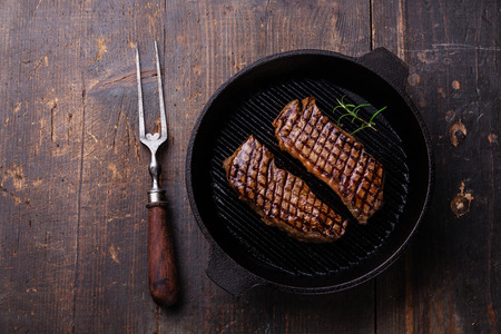 Grilled Striploin steak on grill pan on wooden background
