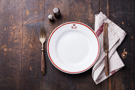 White empty plate and fork and knife on wooden texture background Stock Photo