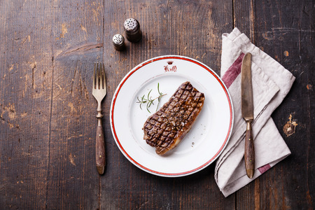 Striploin steak on plate and fork and knife on wooden background