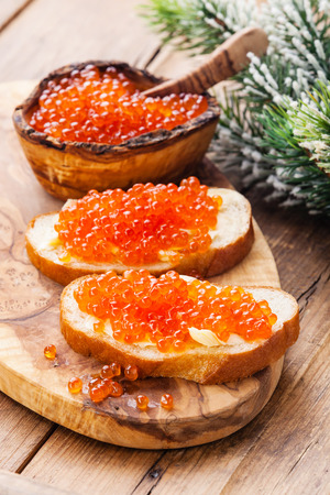 Sandwiches with Salmon red caviar and green Fir Christmas branch on wooden background