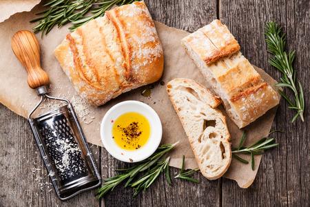 comiendo pan: Rebanadas de pan Ciabatta y aceite de oliva virgen extra en el fondo de madera