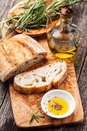 pain: Ciabatta de pain tranch� et l'huile d'olive extra vierge sur le bois d'olive ustensiles fond Banque d'images