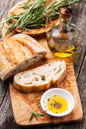 Sliced bread Ciabatta and extra virgin Olive oil on olive wood cookware background