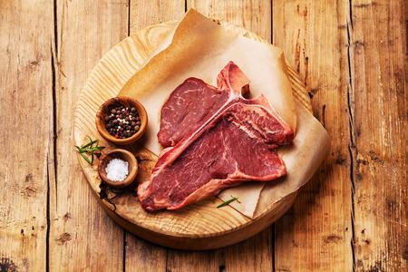 나무 배경에 커팅 보드에 소금과 후추와 원시 신선한 고기 T-bone 스테이크