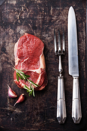 dark meat: Raw fresh meat Ribeye Steak, rosemary and vintage fork and knife carving set on dark background