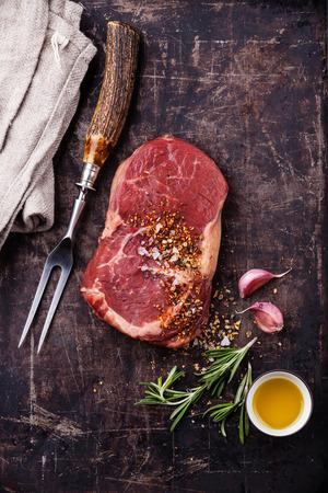 Raw fresh meat Ribeye Steak, seasoning and meat fork on dark background 스톡 콘텐츠