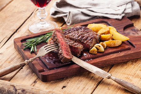 Medium rare grilled Beef steak Ribeye with roasted potato wedges on cutting board on dark wooden background Stock Photo
