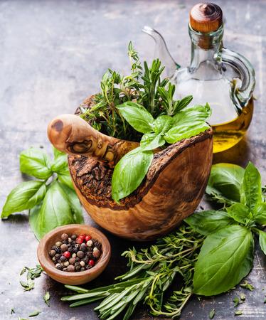 Fresh spicy herbs in olive wood Mortar on dark background Reklamní fotografie