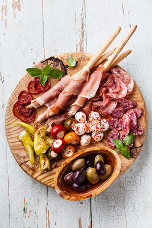 grissini: Cold meat plate with grissini bread sticks on blue wooden background