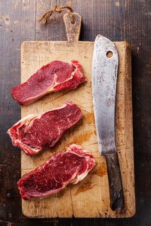 fresh meat: Raw fresh meat Ribeye steak entrecote and meat cleaver on cutting board on wooden background Stock Photo