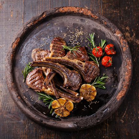 Roasted lamb ribs with spices and garlic on dark textural background Stock Photo