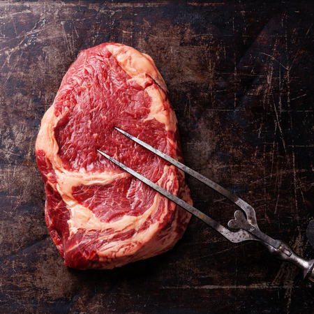 Raw fresh meat Ribeye Steak and meat fork on dark background