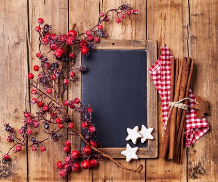 분필 보드, 빨간 열매, 크리스마스 쿠키와 계피 스틱으로 지점 빈티지 크리스마스 배경 스톡 콘텐츠