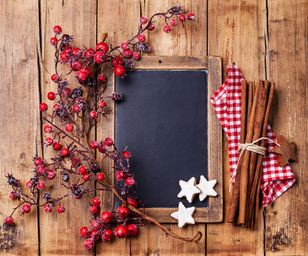 Vintage Christmas background with chalk board, branch with red berries, Xmas cookies and cinnamon sticks