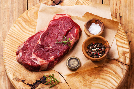 Raw fresh meat Ribeye Steak with salt and pepper on wooden background