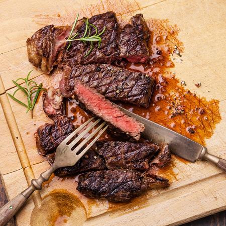 칼과 ribeye 스테이크 구이와 나무 배경에 고기 커팅 보드에 포크