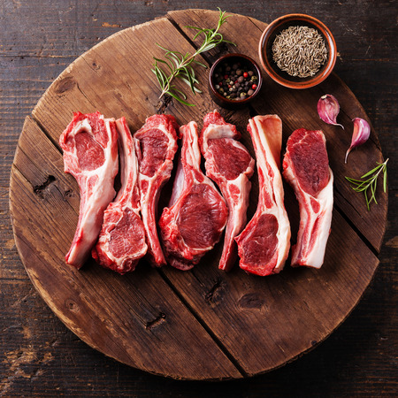 Raw fresh lamb ribs with pepper and cumin on wooden cutting board on dark background Stockfoto