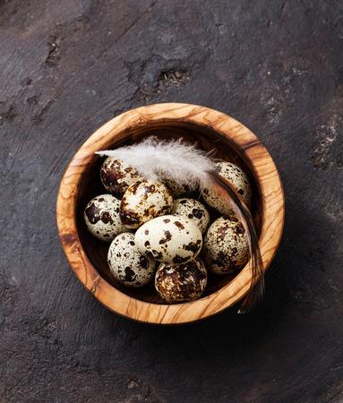어두운 배경에 신선한 메추라기 계란과 올리브 나무 그릇 스톡 콘텐츠