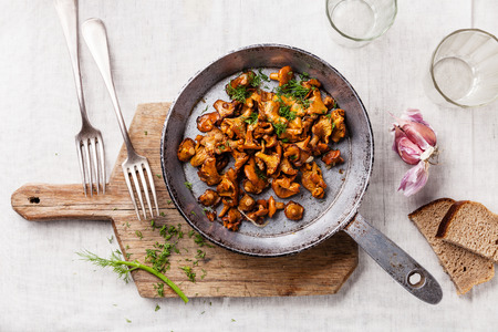Roasted wild mushrooms in pan on white textured background