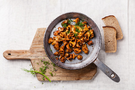 Roasted wild forest  mushrooms in pan on white textured background