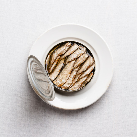 Sprats in can on white textured background