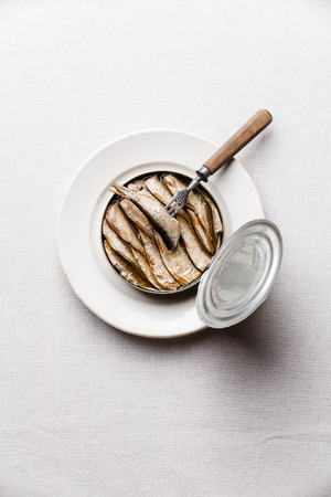 Sprats in can and fork on white background