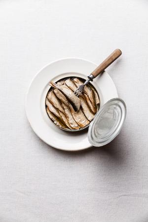 Spratti in lattina e la forchetta su sfondo bianco Archivio Fotografico - 35309909