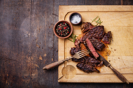 Sliced medium rare grilled Beef steak Ribeye with salt and pepper on meat cutting board on dark wooden background