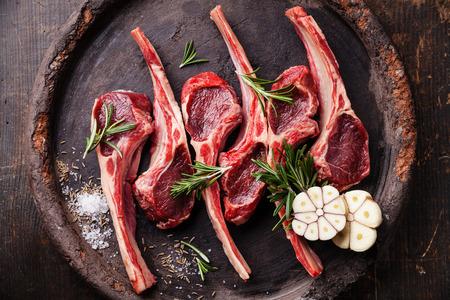 Raw fresh lamb ribs and spicy herbs on dark background Foto de archivo