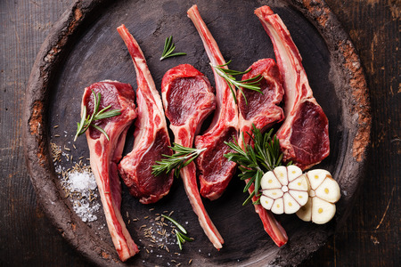 Raw fresh lamb ribs and spicy herbs on dark background Archivio Fotografico