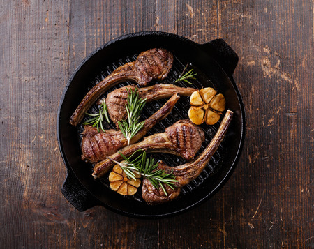 Roasted lamb ribs with rosemary and garlic on grill pan on dark background Imagens