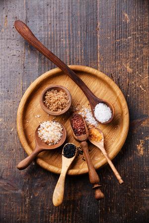 さまざまな種類の食物を粗末暗い背景に木のスプーンの塩