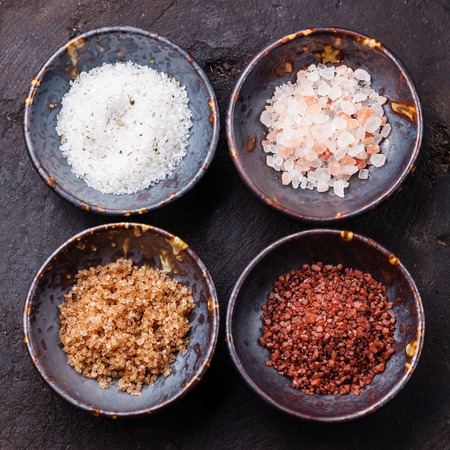 Different types of food coarse Salt in ceramic bowls on dark background