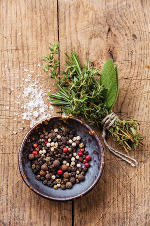 Multicolored peppers peas and spicy herbs on wooden background