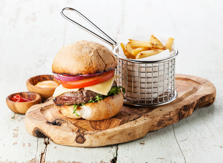 burger background: Burger with meat and French fries in basket on wooden background