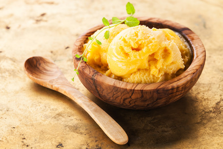 Mango ice cream sorbet in olive wood bowl Stock Photo