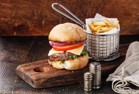 나무 배경에 바구니에 고기와 감자 튀김과 햄버거