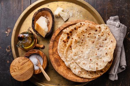 금속 배경에 올리브 나무 접시에 치즈와 함께 튀긴 토르 티아