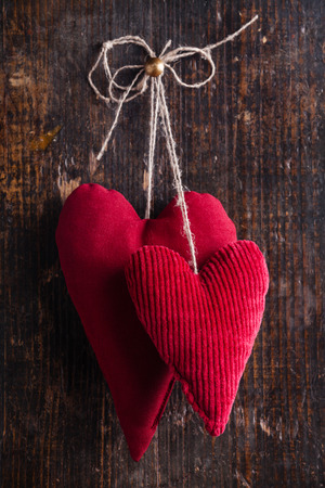Valentines day background with handmade red hearts hanging on wooden background 写真素材