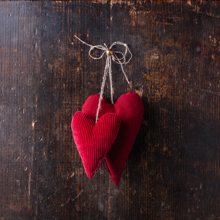 Valentines day background with handmade red hearts hanging on wooden background Reklamní fotografie