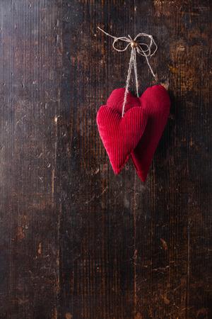 나무 배경에 매달려 손수 빨간 마음으로 발렌타인 배경