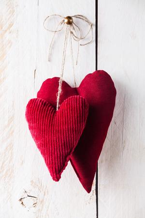 白い木製の背景に掛かっている手作りの赤いハートのバレンタインの日の背景