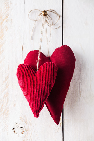 Valentines day background with handmade red hearts hanging on white wooden background