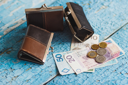 zloty: Polish zloty with three wallets on the wooden background Stock Photo