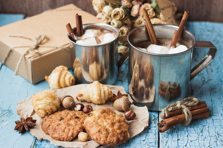 Metal mugs with cacao and marshmallow, different cookies and decorations near mugs, wooden background